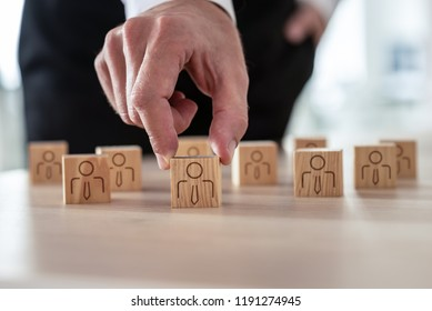 Human resources concept - businessman arranging wooden cubes with people icon on office desk.