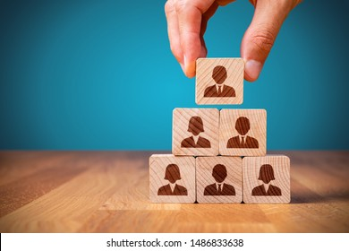 Human resources, corporate hierarchy concept and multilevel marketing - recruiter complete team represented by wooden cube by one leader person (CEO) and icon.