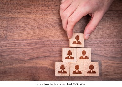 Human resources, corporate hierarchy concept and multilevel marketing - recruiter complete team represented by wooden cube by one leader person (CEO) and icon, flatlay design.