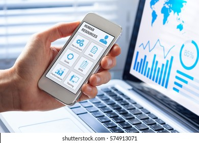 Human resources (HR) management app concept on a mobile phone screen with a person hand and office interior background, icons about recruitment, hiring, jobs, training