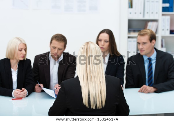 Human resources team conducting an interview reading the credentials of a blond business applicant sitting with her back to the camera