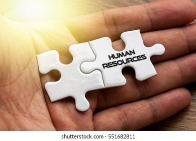 HUMAN RESOURCES written on White color of jigsaw puzzle with hand,conceptual