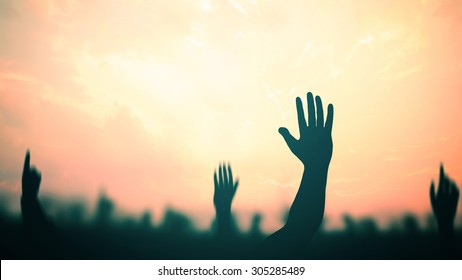 Human rights concept: Silhouette many people raised hands over sunset background