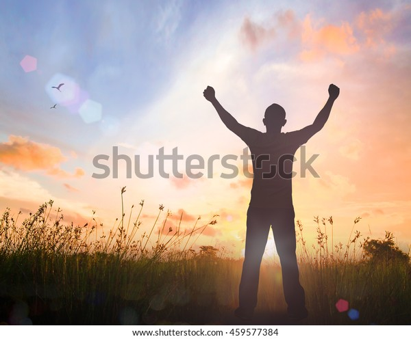 Human rights day concept: Silhouette of man raised hands at meadow autumn sunset background