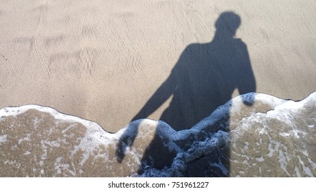 Human shadow in the shoreline.