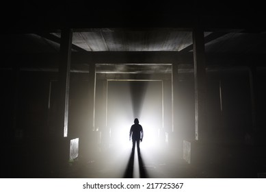 A human silhouette in an abandoned hallway.