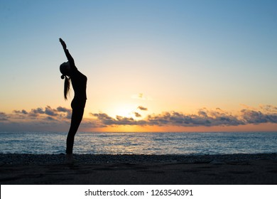 Human silhouette doing yoga on the beach at the dawn. Woman rise her hands up and greeting to the rising sun, harmony, spiritual awakening and peace concept