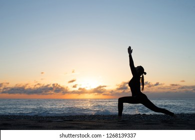 Human silhouette doing yoga on the beach in front of rising sun, woman stands in warrior pose, hands up. Wellness and activity concept