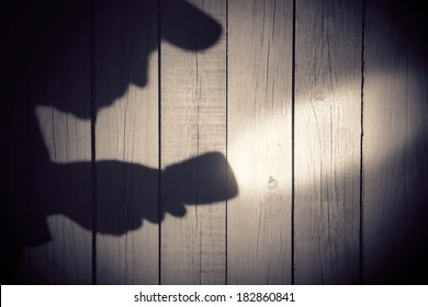Human silhouette with flashlight in shadow on wood background, with space for text or image.