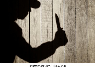 Human Silhouette with Knife in Shadow on wooden background, with space for text or image.