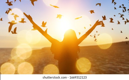 Human silhouette raises hand up on sunset sky background