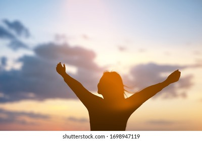 Human silhouette with raising hands on the sunset background