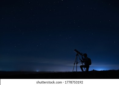 Human silhouette and telescope, a woman looks through a telescope at the starry sky. Night sky, stars, long exposure, astronomy