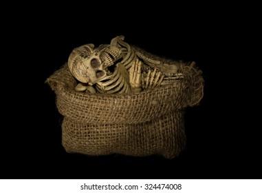 Human skeleton bones in sack on black background