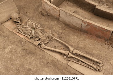 Human skeleton next to an empty open tomb on dirty sand
