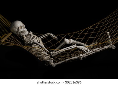 Human skeleton swinging on hammock