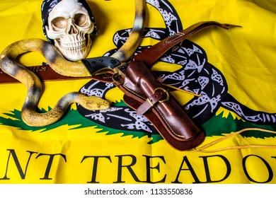 human skull with black skull cap leather holster with black revolver and large yellow snake on yellow tread on me flag