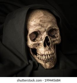 Human skull in black hood as image of death