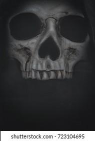Human skull in hood on dark background. Halloween grunge banner