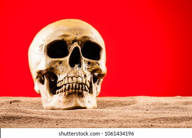 A human skull lying on the sand with a red post-apocalyptic sky as background. Could be a metaphore for global warming or hell.