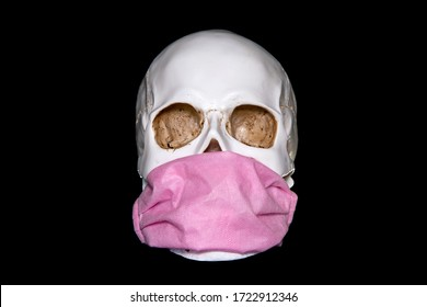 A human skull In Medical Mask on a dark background. Concept Of Deadly Coronavirus Epidemic.