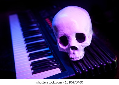 Human skull on electric piano keyboard for scary musical performance