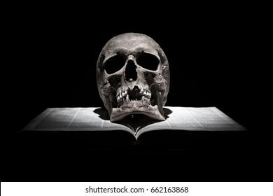 Human skull on old open book on black background under beam of light