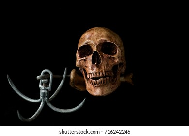 Human skull placed on a black background scene. There is a hook.