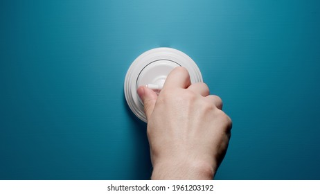 Human Switches On A Toggle Switch On The Blue Wall
