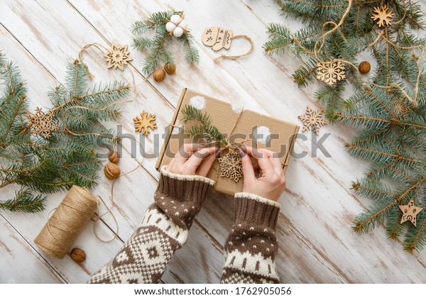 Human takes Christmas craft gift box with xmas wooden toys on wooden background. Handmade christmas gift. Top view. Christmas eve preparation. Woman's or kid's hands paking present box. Natural rustic