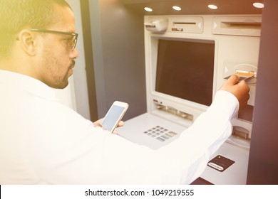 Human and technology. Dark skinned man using ATM. Black guy's hand inserting plastic bank card into cash dispenser or ATM machine selective focus
