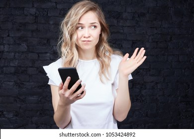 Human and technology. People, education concept. Beautiful European woman in casual clothes studying at classroom having some doubts checking information in telephone using internet. Face expression.