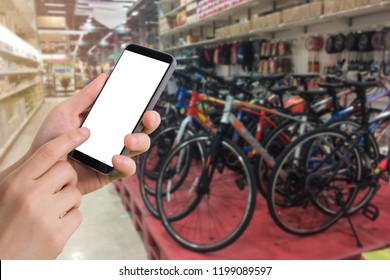 human touching blank screen on smartphone with blurry bicycle shop background. concept of shopping sport items.