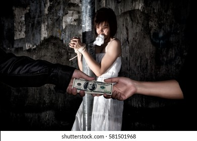 Human trafficking concept., Person hand with a dollar banknote buying victim woman in pain and bound hands with rope., missing kidnapped., in dark tone.