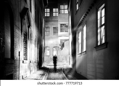 A human wanders through a spooky narrow alley in the dark night