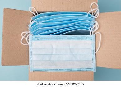 Konzept der humanitären Hilfe. Oben oben über Kopf, Nahaufnahme von einem offenen, ungepackten Papierkasten mit vielen medizinischen Masken auf blauem Hintergrund