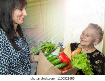 Humanitarian assistance to a pensioner from a social worker;  woman assisting elderly lady with her everyday routine; The product basket for the pensioner.