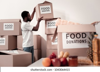 Humanitarian help. Concentrated brunette holding box and raising hands while standing in semi position