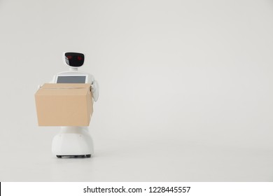 Humanoid autonomous robot with cardboard box in hand on white background. the robot delivers the parcel. delivery concept.