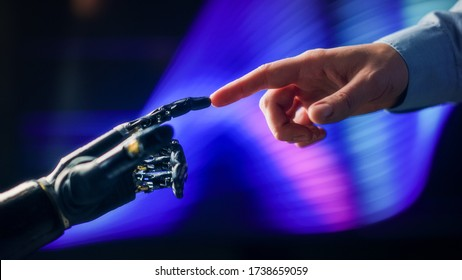 Humanoid Robot Arm Touches Human Hand Connecting Fingers. Humanity and Artificial Intelligence Unifying Gesture.Technology Merges with Creative Human Mind. Inspired by Michelangelo's Creation of Adam