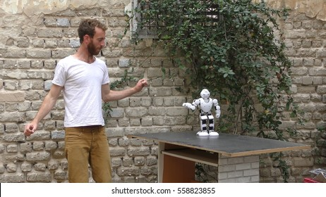 A humanoid robot teaches a young man the art of dancing. The robot has a lot of patience and it repeats the same movements precisely.