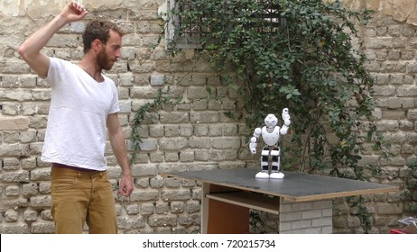 A humanoid robot teaches a young man to dance. The man sees the robot via head mounted display. The robot has a lot of patience and it repeats the same movements precisely.