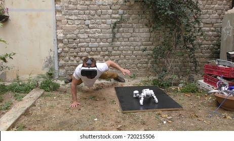 A humanoid robot and a young man exercise push ups because they want to be fit. The man sees the robot via head mounted display. The robot has a lot of patience and it repeats the movements precisely.