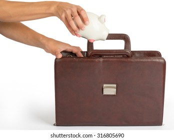 Humans hand holding piggy bank and suitcase on isolated white background