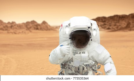 Humans on the planet Mars. Astronaut on Mars shows a thumbs-up. Landscape of the red planet Mars. Spaceman inhabits a new planet