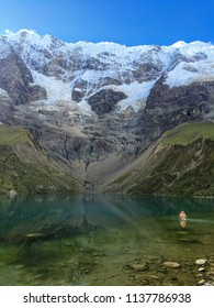 Humantay Lake, Cusco, Peru - May 7th, 2016.  A young traveler takes a cold dip in the frigid waters of the glacial Humantay Lake, hidden beside Salkantay Mountain deep in the Peruvian Andes.