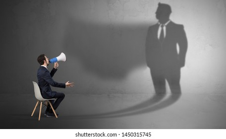 Humble businessman staying and offering stuffs to a huge businessman shadow