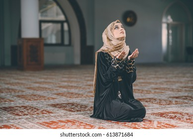 Humble Muslim woman holding hands up and praying in peace