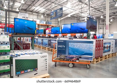 HUMBLE, TX, US-NOV 25, 2016: Costco Wholesale with row of big screen, smart TVs display on shelves and on flatbed cart. Largest membership-only warehouse club in US with total of 705 stores worldwide