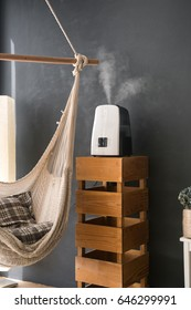 Humidifier in the modern interior of the apartment. Vapor from humidifier in the morning light in a living room In the style of a loft and rustic.